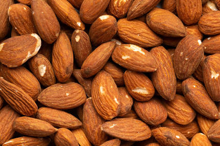 Many beautiful almond nuts as a background