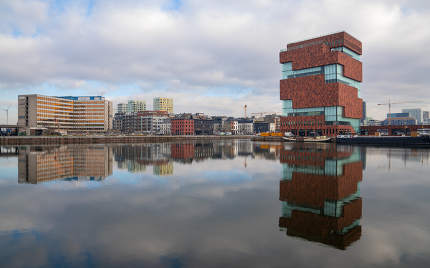 Modern buildings around the old city harbor with reflection in the water on February 6, 2020 in Antwerp, Belgium