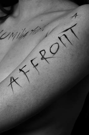 part of a young woman's body with the words affront,cruelty,inequality on a black background.photo.the inscription is not a tattoo, written by the photographer's hand