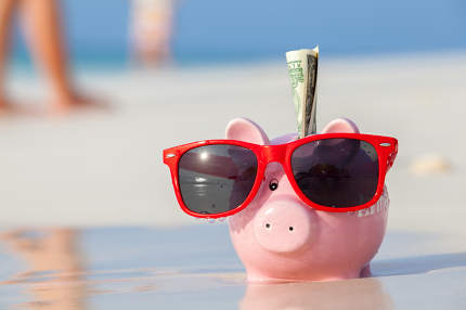 Pink pig moneybox in red sunglasses on the beach