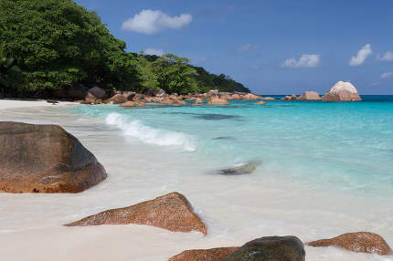Seychelles with a turqouise water and big stones and lot of gree