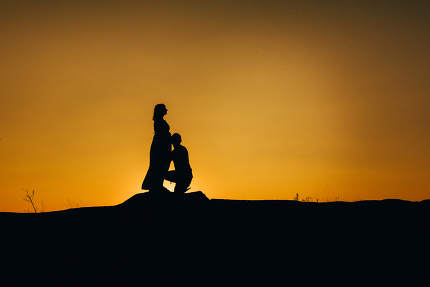 silhouettes of a happy young happy family against an orange suns