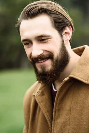 smiling man in a brown coat