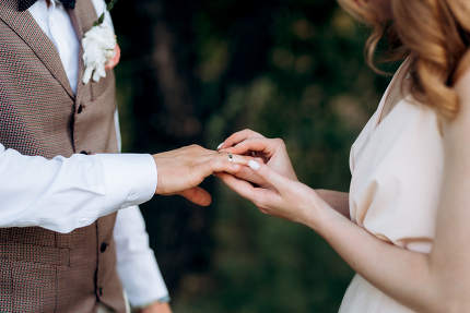 the bride and groom held hands with wedding rings