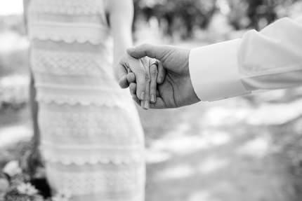 the bride and groom tenderly hold hands between them love and re
