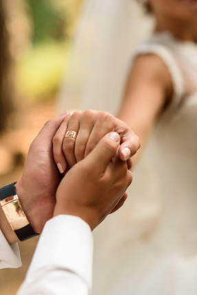the groom holds the bride's hand