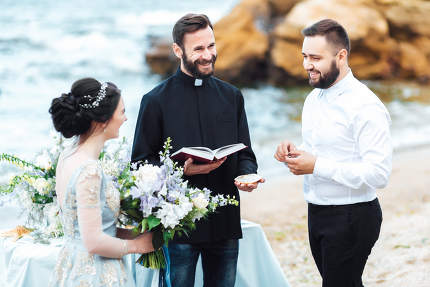 wedding couple on the ocean with a priest