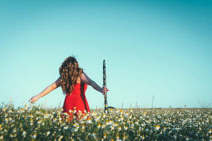 woman in a red dress and a clarinet enjoying freedom in a field of daisies