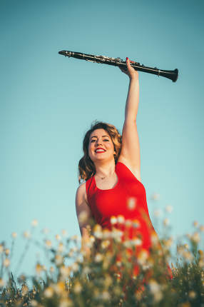 woman in a red dress raising a clarinet in a field of daisies