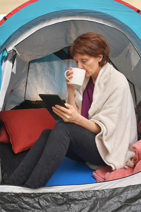 Woman sit inside a tent enjoying a cup of tea