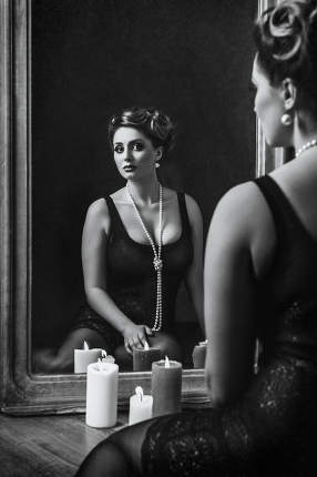 young brunette model girl and actress in front of a mirror, blac