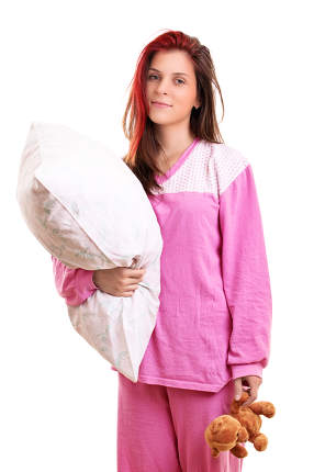 Young girl in pajamas holding a pillow and a teddy bear