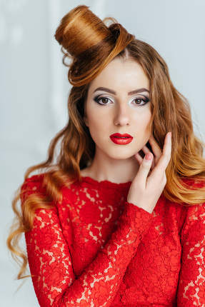 young girl with red hair in a bright red dress in a light room
