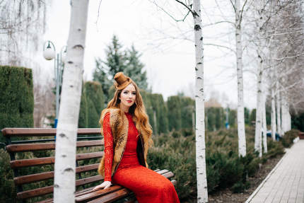 young girl with red hair in a bright red dress on a bench in an