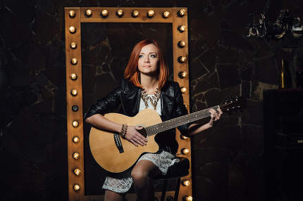 young girl with red hair with an acoustic guitar