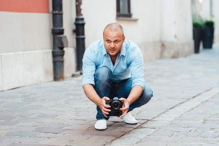 young guy, photographer walking in the old streets of europe