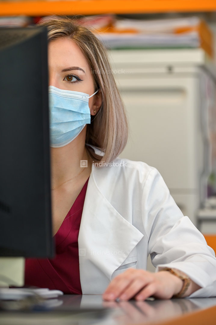 A Doctor In A Mask Works On A Computer