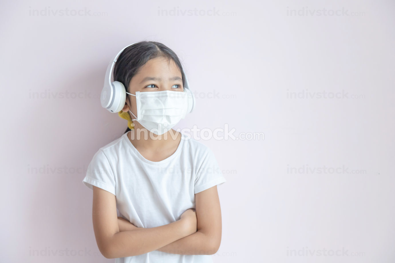 A little Asian girl wearing a medical protective mask and earpho