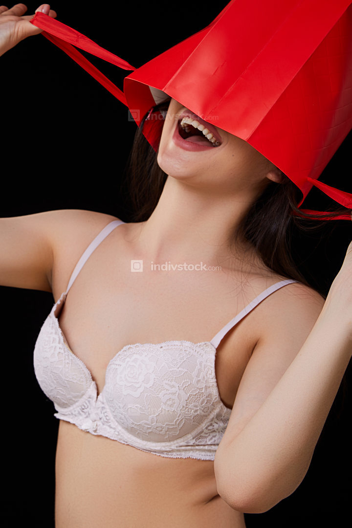 a young beautiful woman in white underwear with a red paper shopping bag poses and smiles. on a black isolated background