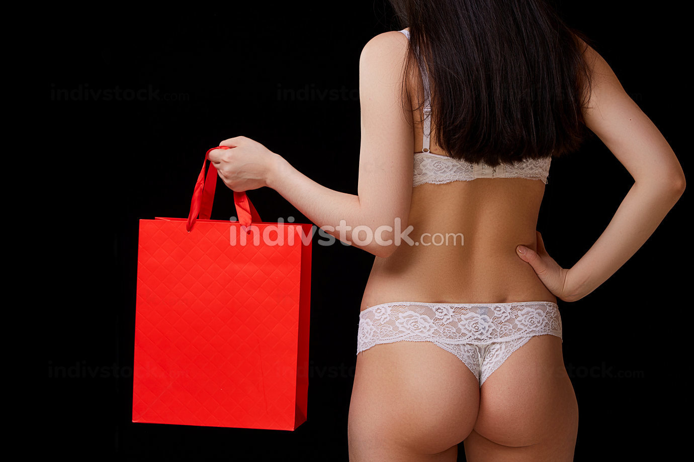 a young beautiful woman in white underwear with a red paper shopping bag poses. on a black isolated background