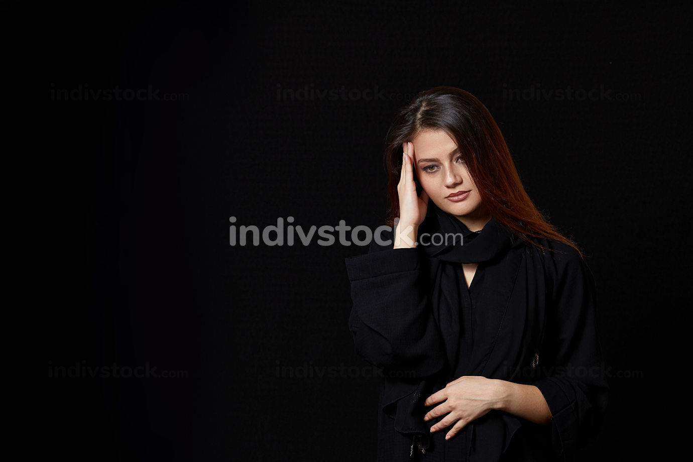 a young brown-haired woman in black clothes holds her head. thinks or has a headache. on a black isolated background.