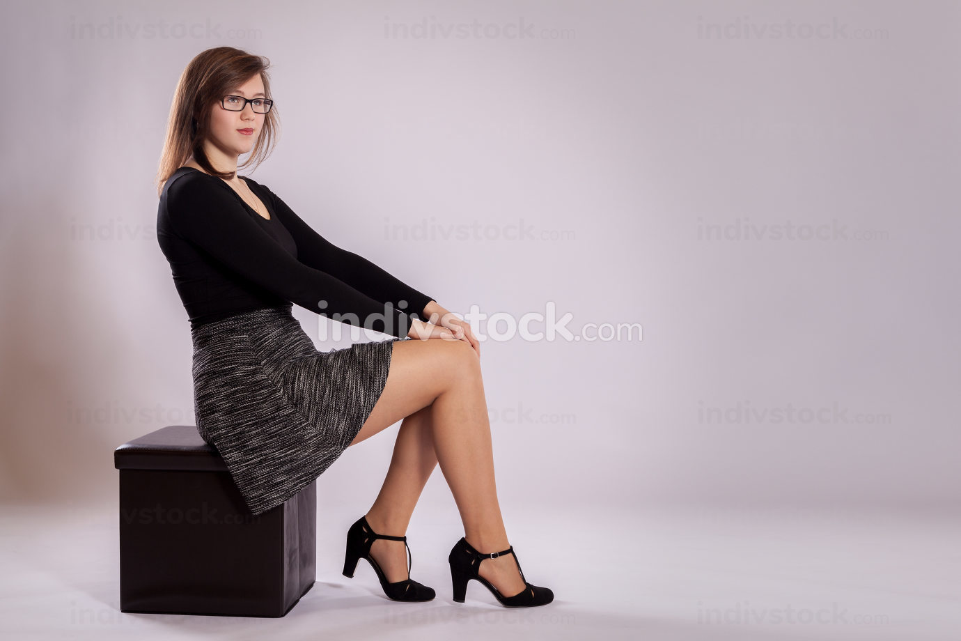 A young girl is sitting on a stool