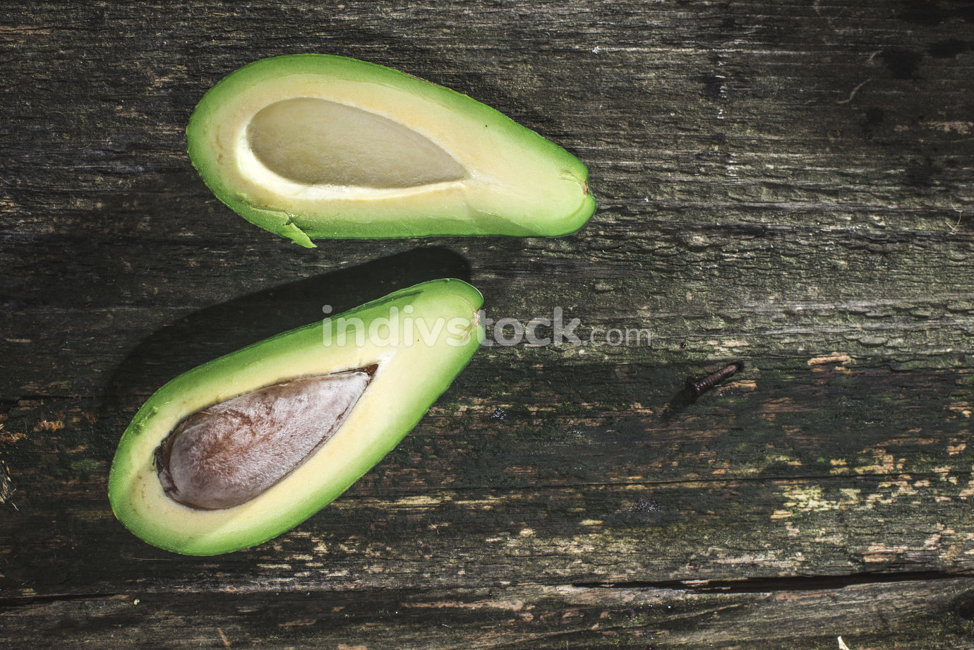 Avocado on wood. Dirrect sunlight