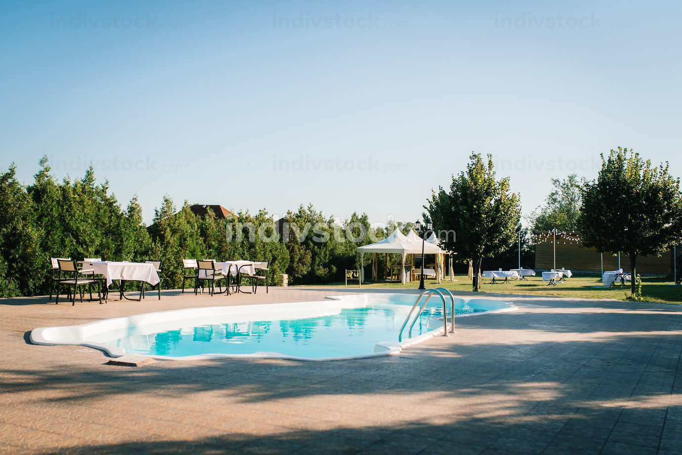 blue outdoor pool in the garden surrounded by trees