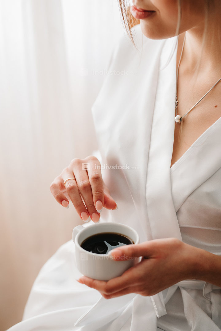 bride drinking cappuccino on the background of painted tableclot