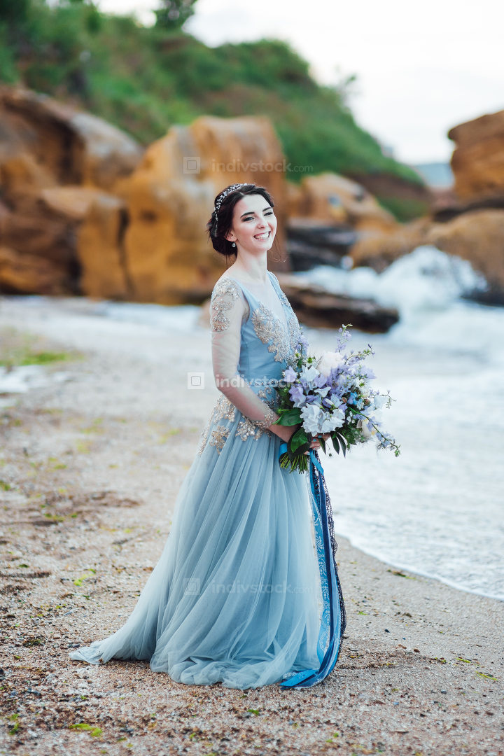 bride with a bouquet of flowers on the beach