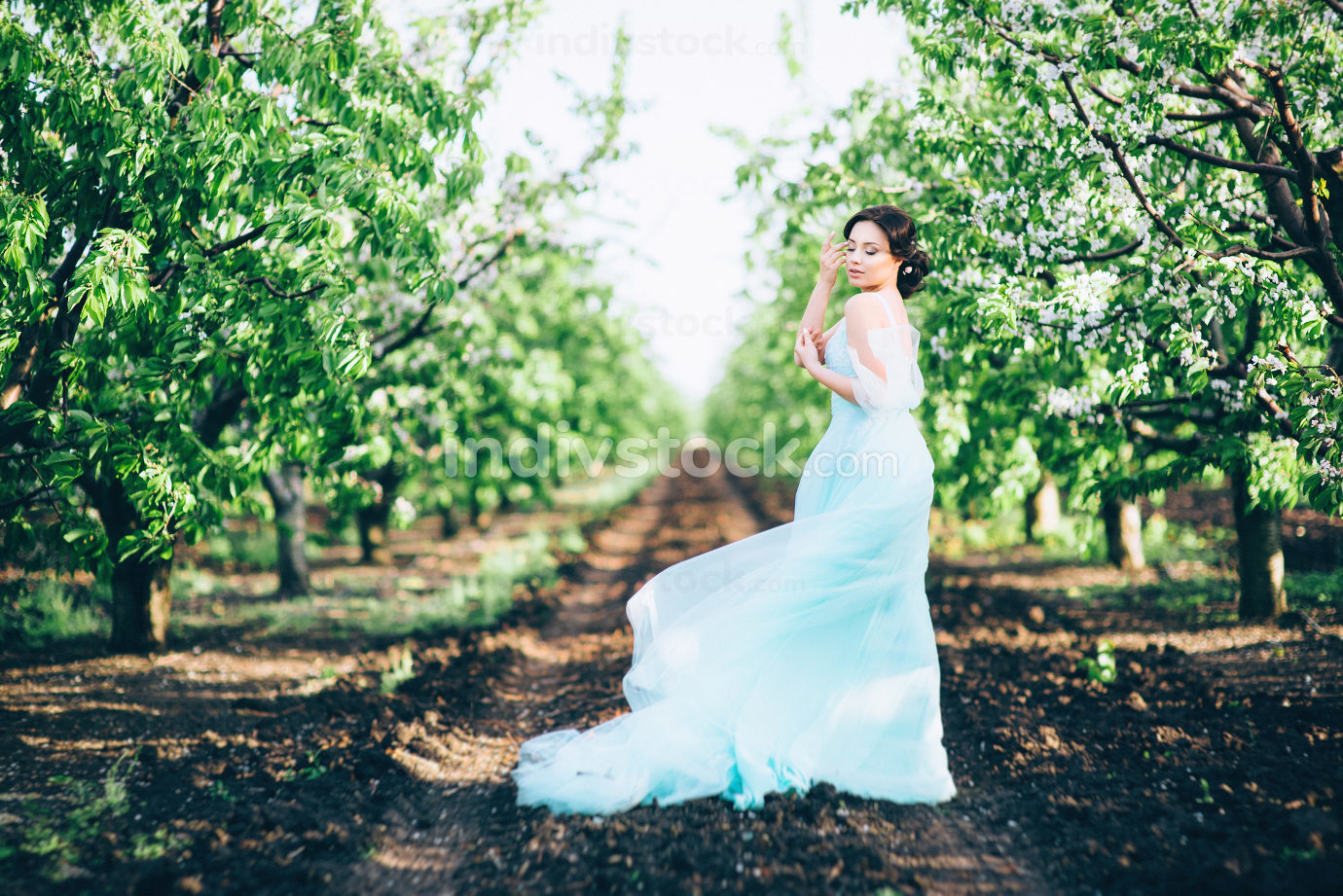 brunette girl in a turquoise dress in the spring garden