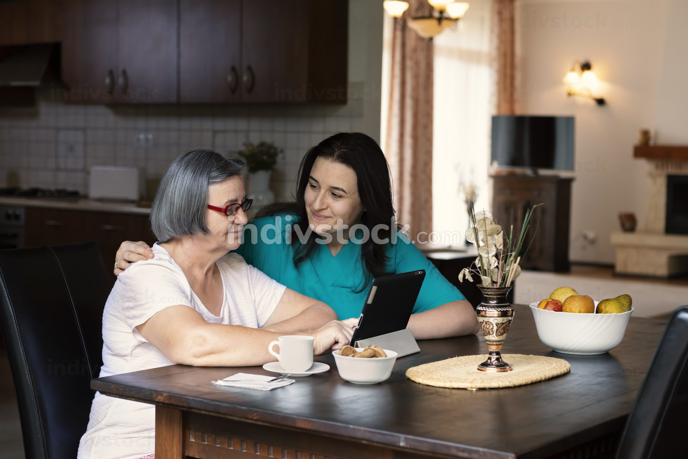 Caring nurse showing a digital tablet to an elderly woman in a n