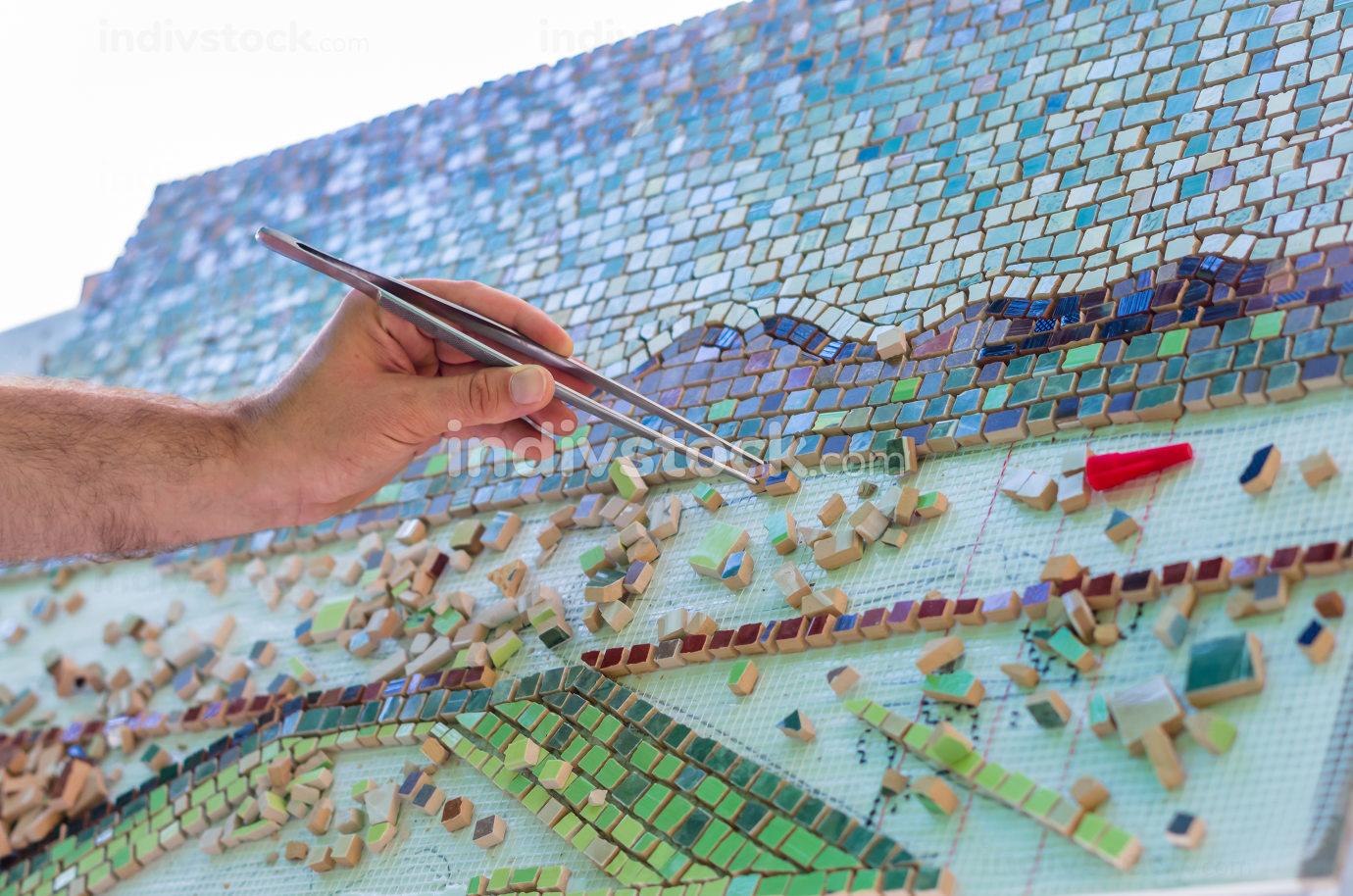 Ceramic design. Ceramic mosaic. The man organizes with a tweezer