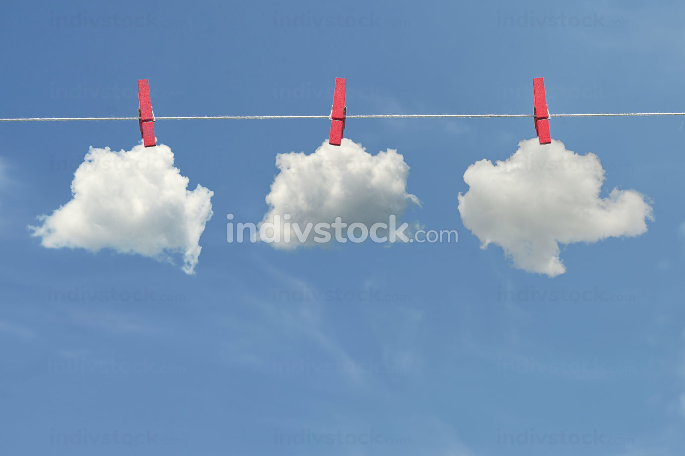 Clips for laundry hanging clouds on a string rope on blue sky