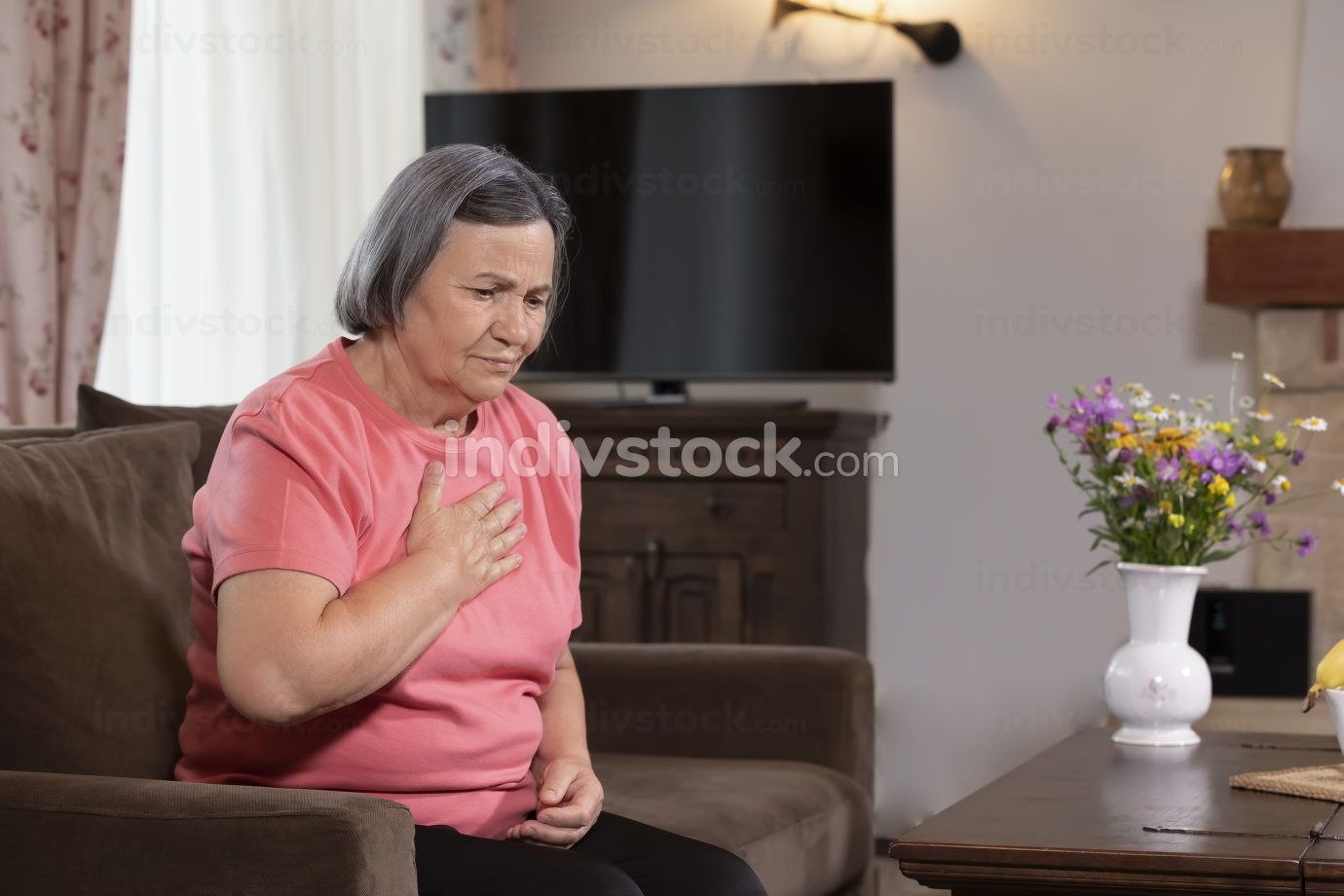 Elderly woman having a heart attack at home