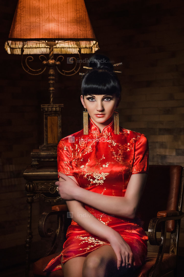 girl in a red Japanese silk dress qipao in a dark room