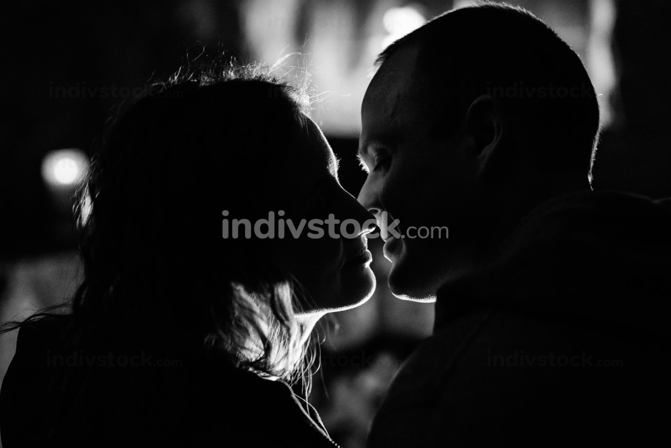 guy and girl are sitting on the background of a burning fireplac