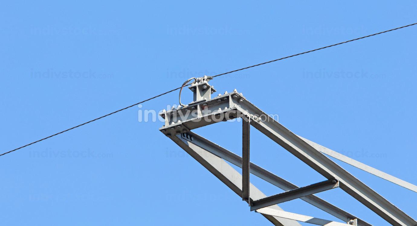 High-voltage electricity pylon against blue sky