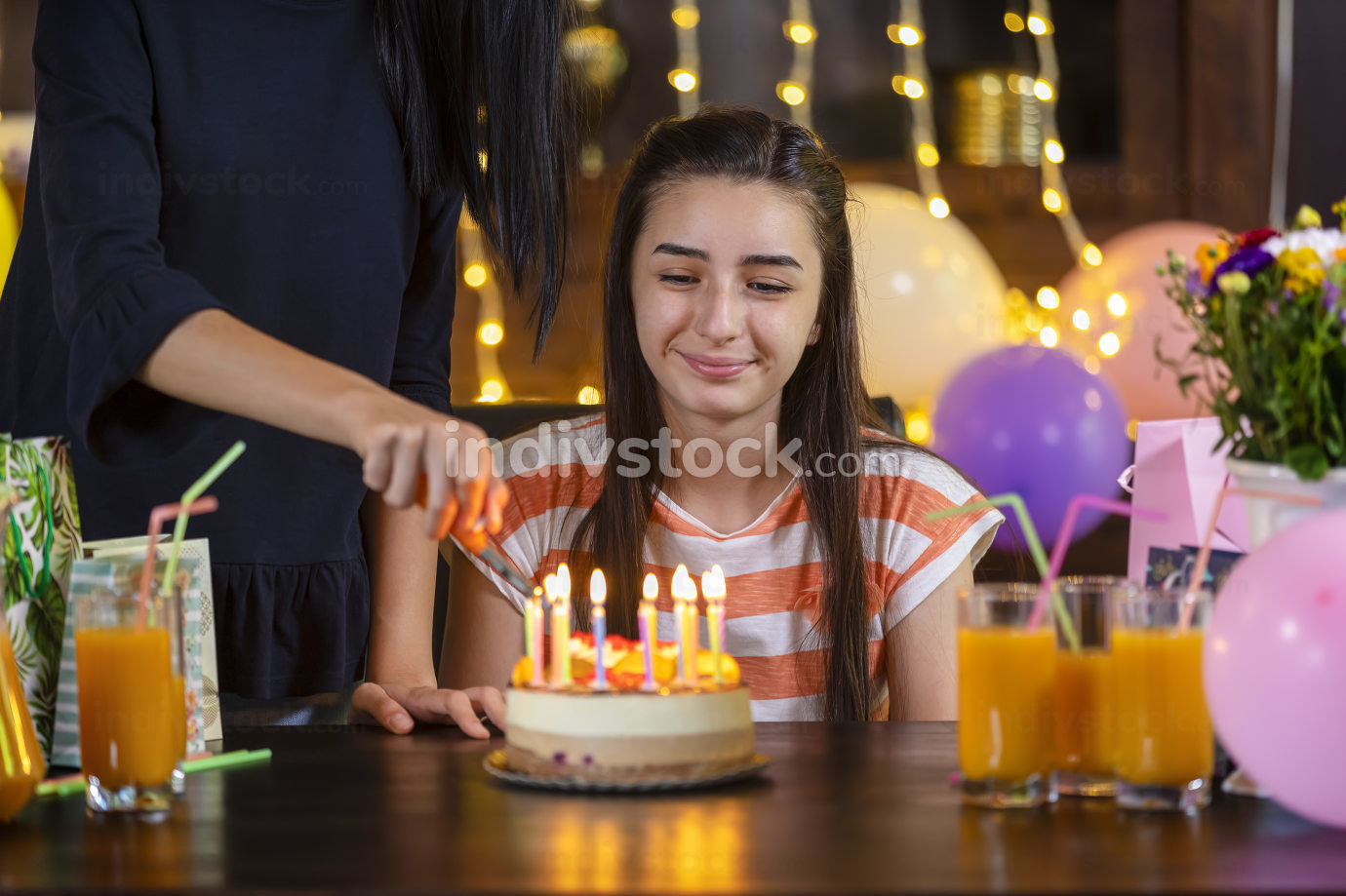 Mother lighting candles on her daughter birthday cake at party