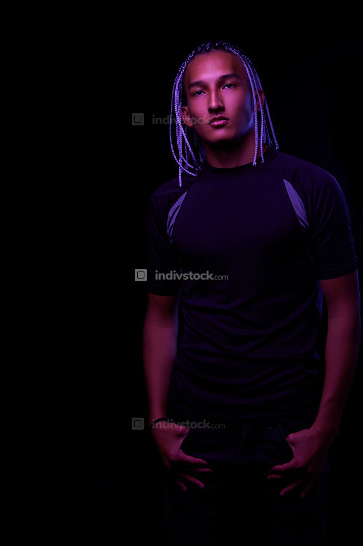 portrait of a young naked african man at studio. High Fashion male model in colorful neon bright lights posing on black background. Art design concept. selective focus