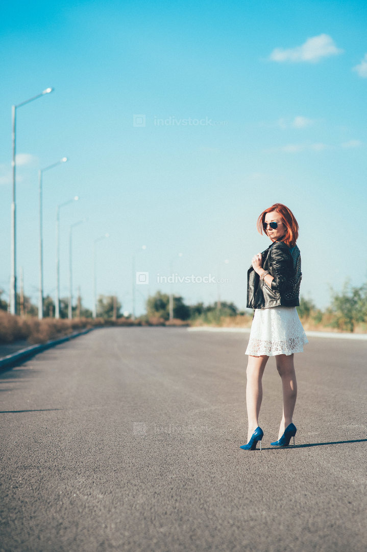 red-haired girl in a black jacket and blue glasses