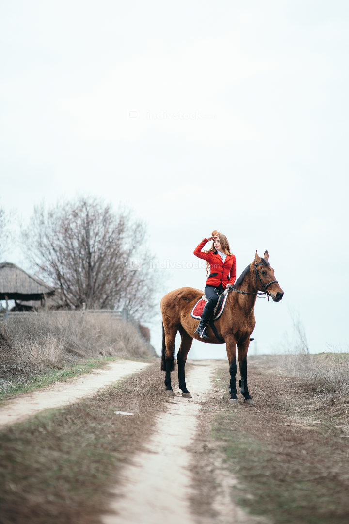 red-haired jockey girl in a red cardigan and black high boots wi