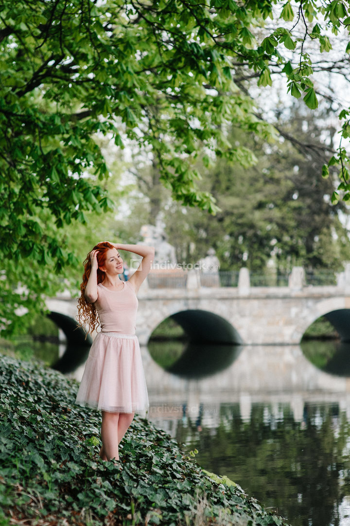 red-haired young girl walking in a park between trees