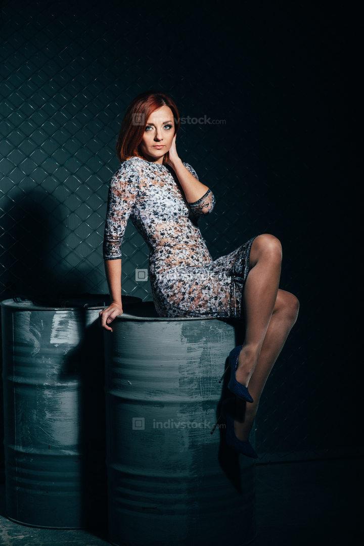 redheaded model girl in a long dress in a dark industrial Studio