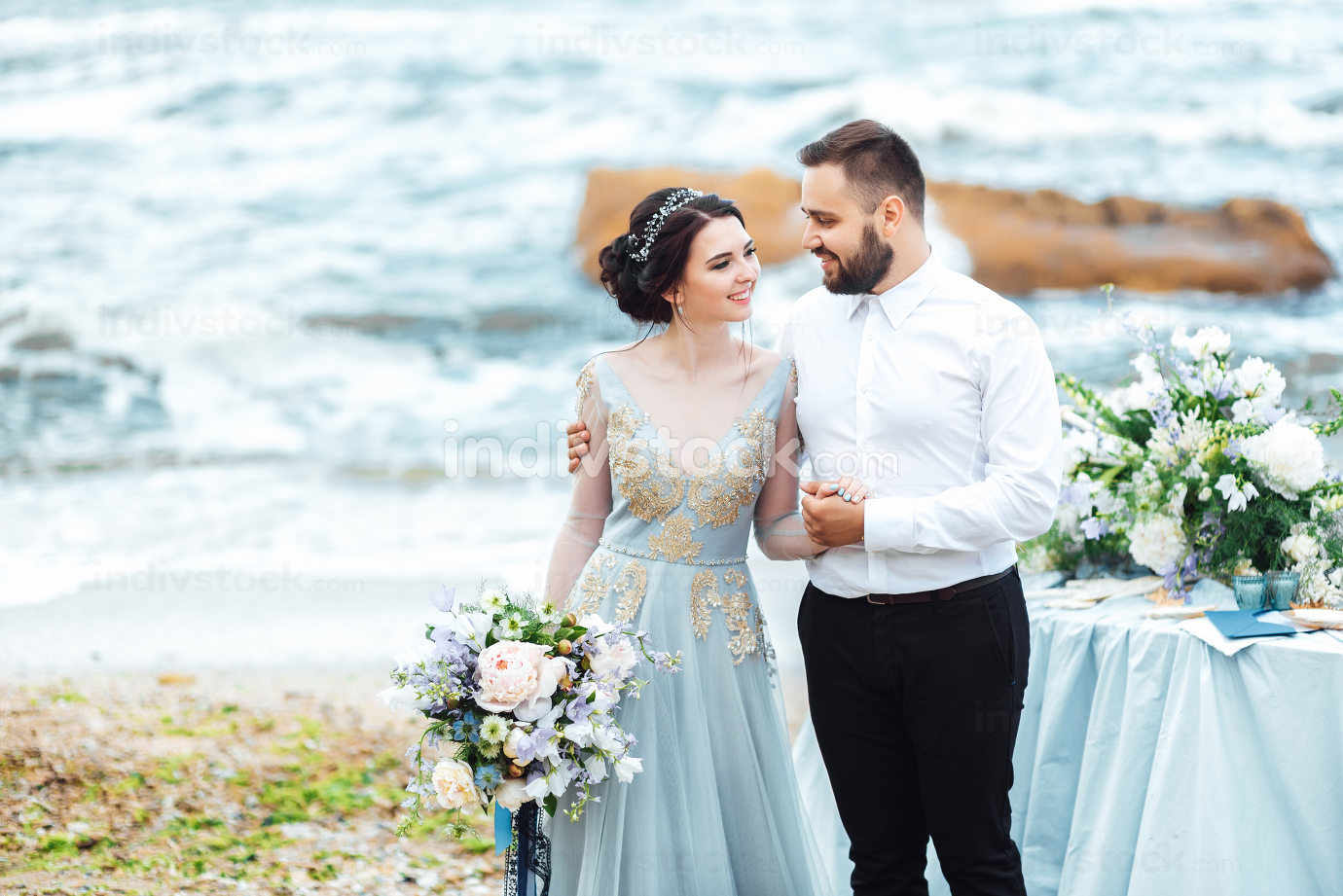 same couple with a bride in a blue dress walk