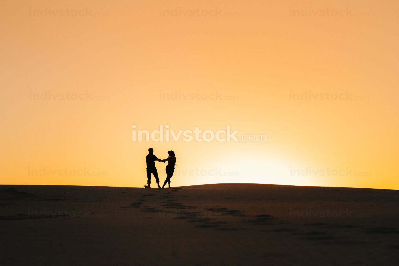 silhouettes of a happy young couple on a background of orange su