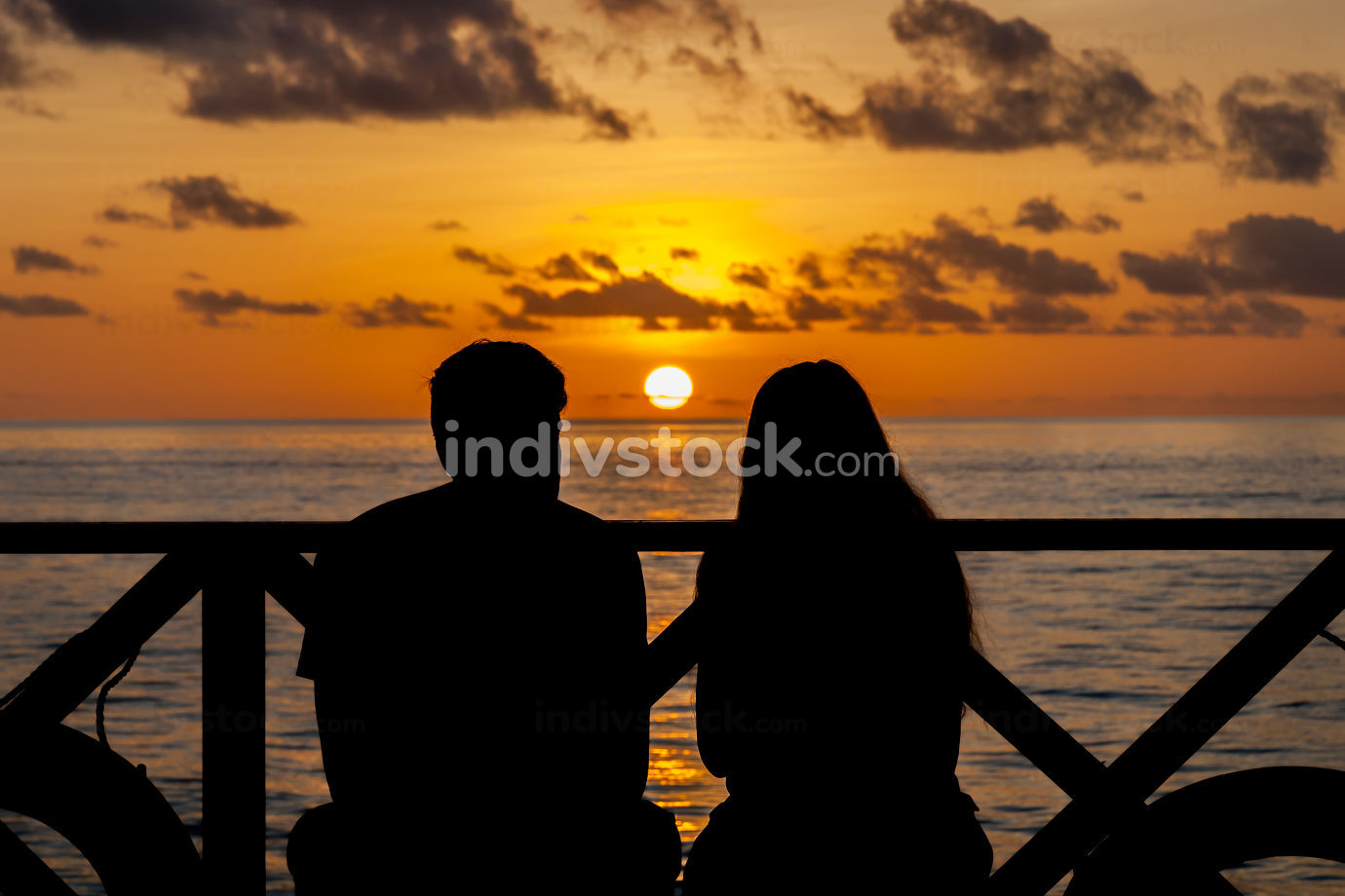 Sunset on the Maldives, a couple on the beach looking in the dis