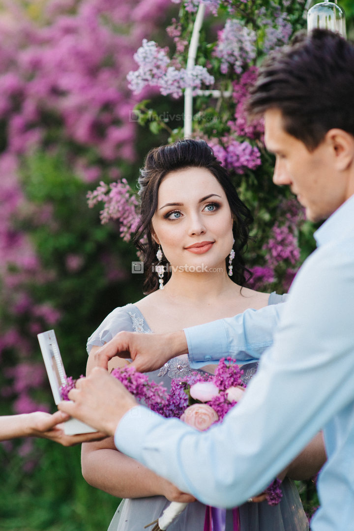 the groom dresses the bride with wedding rings