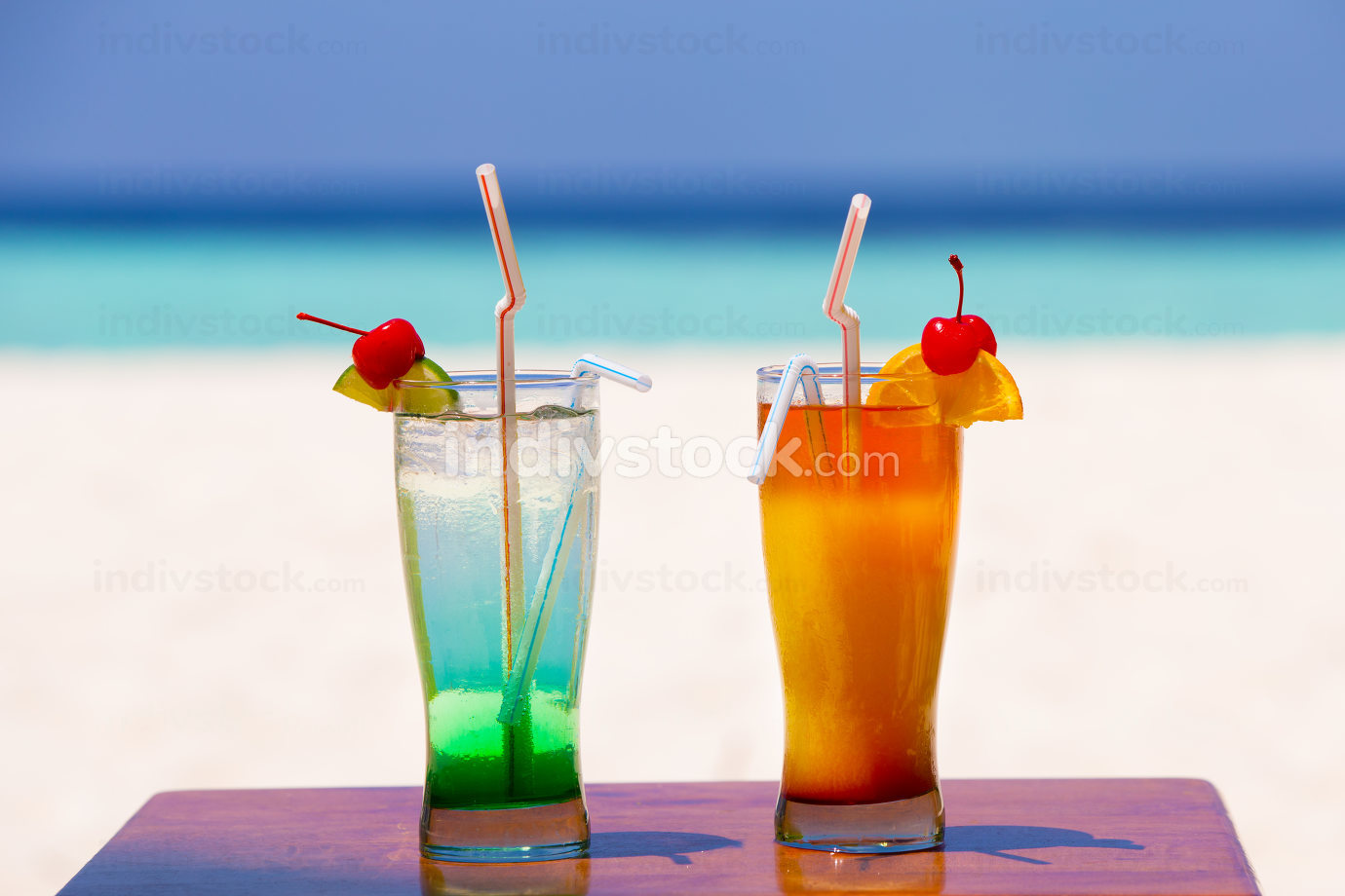 Two colorful cocktails on the beach of an island