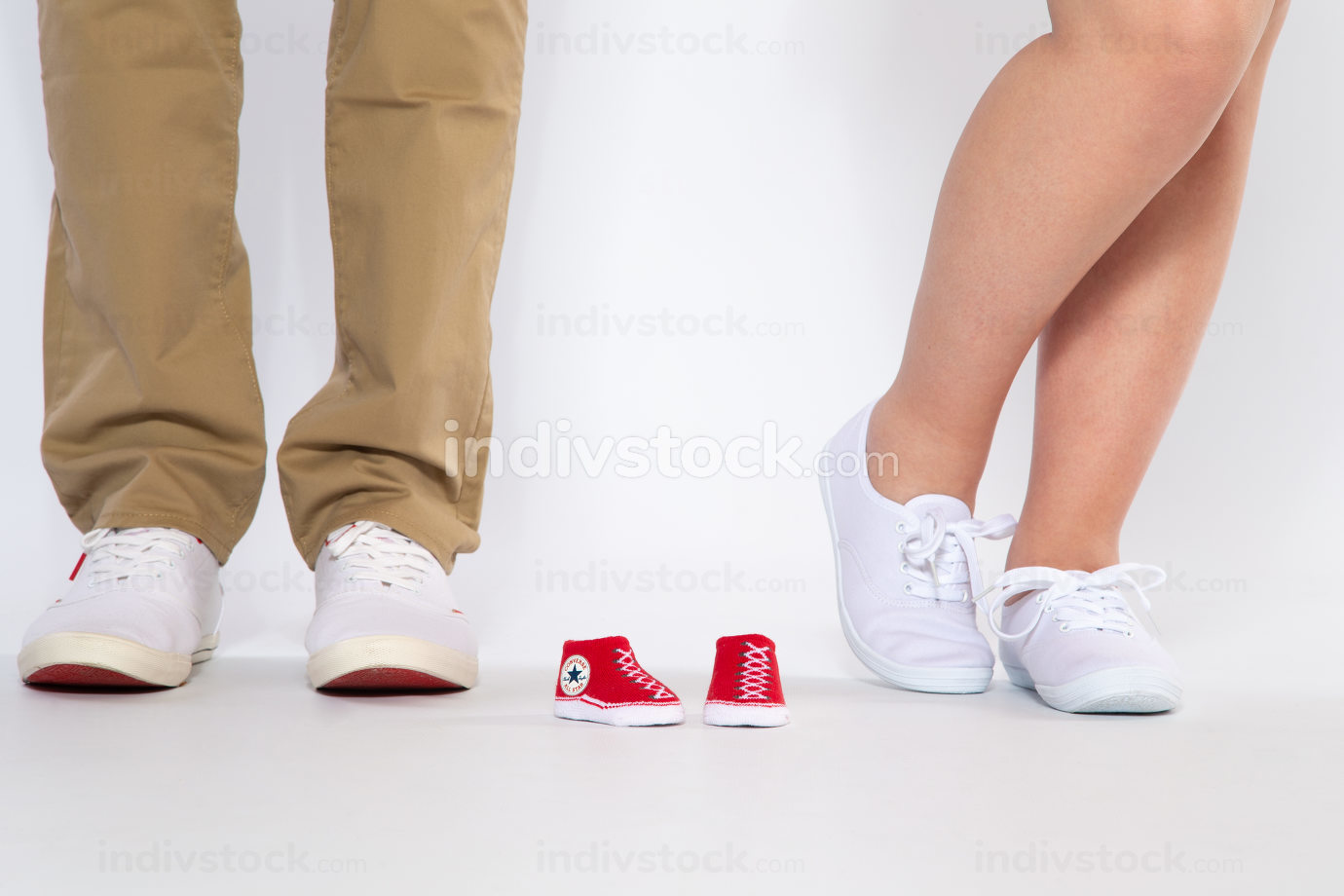 Two pairs of feet from the parents and shoes from an unborn baby